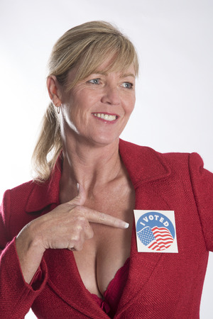 ladies bust: Woman points to a voting sticky label attached to her jacket lapel