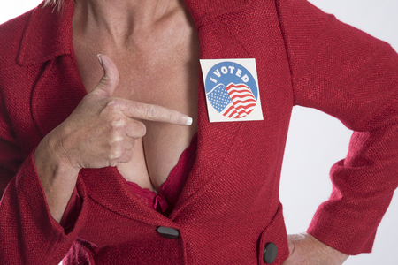 lapel: Woman points to a voting sticky label attached to her jacket lapel