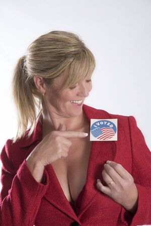 attached: Woman points to a voting sticky label attached to her jacket lapel