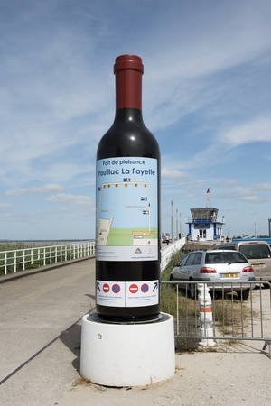 gironde: A large bottle of red wine at the entrance to Port Pauillac La Fayette on the River Gironde southwest France Editorial