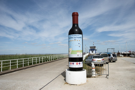 A large bottle of red wine at the entrance to Port Pauillac La Fayette on the River Gironde southwest France Editorial