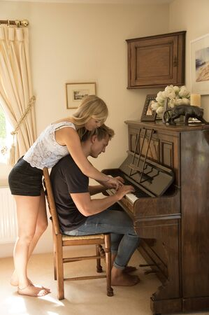upright piano: Couple playing the piano - August 2016 - Two young teenagers playing an upright piano