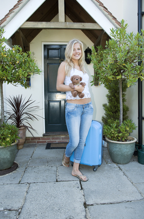 Teenager leaving home - August 2016 - Blond attractive girl leaving a house with a suitcase and a toy bear
