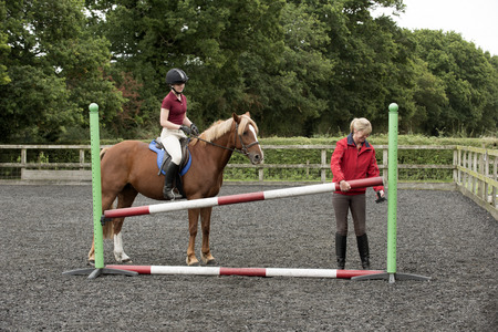 erecting: Erecting a jump in an outdoor riding school - September 2016 - Riding instructor lifting a pole to increase the height of the fence for the pupil riding a Chestnut pony