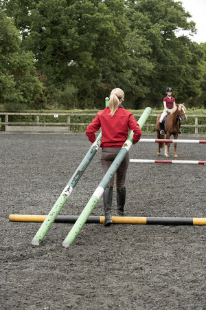 erect: Erecting a jump in an outdoor riding school - September 2016 - Riding instructor carrying plastic poles to erect a fence in the riding school