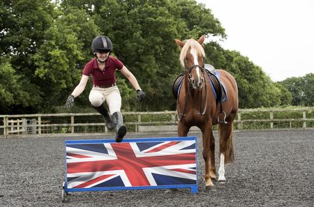 salto de valla: Un jinete de caballo joven saltando una valla baja - Septiembre 2016 - Una Castaña relojes pony como el jinete salta una valla baja