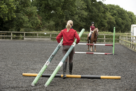 erecting: Erecting a jump in an outdoor riding school - September 2016 - Riding instructor carrying plastic poles to erect a fence in the riding school
