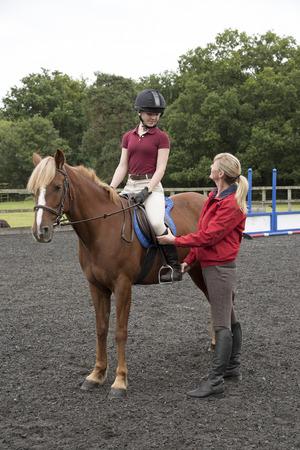 Giovane cavaliere cavallo seduto in sella - Settembre 2016 - Adolescente imparare a guidare con l'istruttore Archivio Fotografico - 63072607