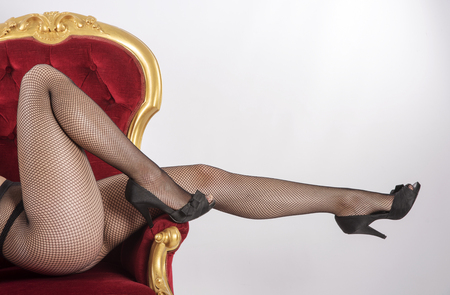 Womans legs in fishnet tights seated on a velvet and gold painted chair