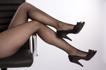 fishnet tights: Womans legs wearing fishnet tights Stock Photo