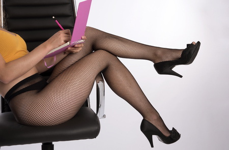 secretarial: Womans legs wearing fishnet tights Stock Photo
