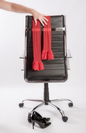 Frau an der Hand Platzierung roten Strümpfen auf einem Executive Bürostuhl mit einem Paar schwarze High Heels