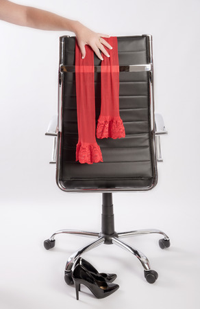 Womans hand placing red stockings on an executive office chair with a pair of black high heels