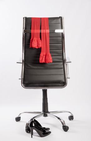 Rote Strümpfe auf einem Executive Bürostuhl mit einem Paar schwarze hgih Fersen