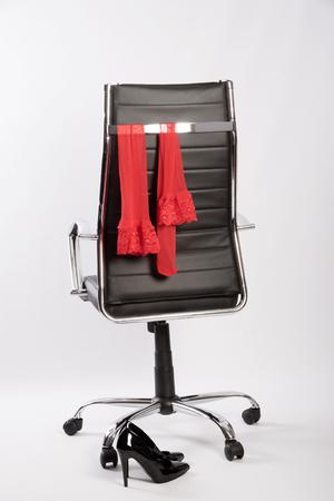 Rote Strümpfe auf einem Executive Bürostuhl mit einem Paar schwarze hgih Fersen Standard-Bild