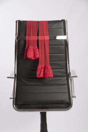 Rote Strümpfe auf einem Executive bllack Bürostuhl