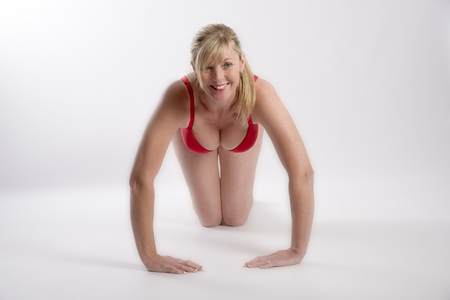 buxom: Middle aged woman exercising. A blond attractive woman doing press-ups