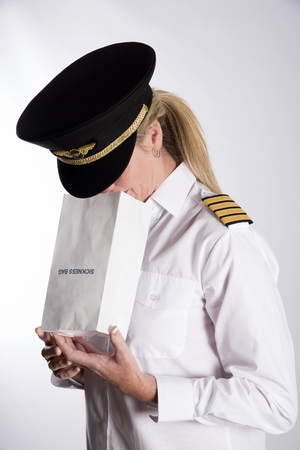 nauseous: Woman using a sickness bag - September 2016 - A uniformed female pilot feeling nauseous using a paper sickness bag