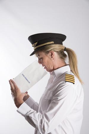 Vrouw met behulp van een ziekte zak - september 2016 - Een geüniformeerde vrouwelijke piloot misselijk met een papieren zak ziekte