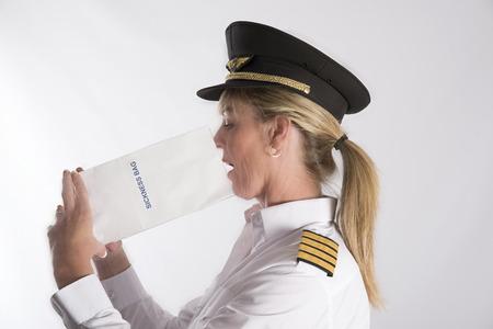 sickly: Woman using a sickness bag - September 2016 - A uniformed female pilot using a paper sickness bag Stock Photo
