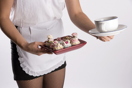 fishnet tights: Young attractive waitress in uniform - August 2016 - A waitress serving a tray of cakes and a cup of tea Stock Photo