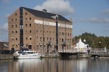 Gloucester Docks Gloucestershire England UK - October 2016 - An old warehouse converted into apartments sitting waterside on the main basin of Gloucester Docks
