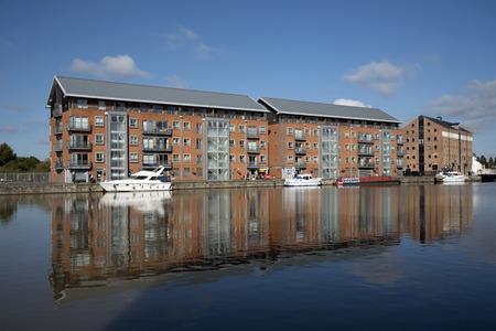 Gloucester Docks Gloucestershire England UK - October 2016 - New build apartment blocks sitting waterside on the main basin of Gloucester Docks