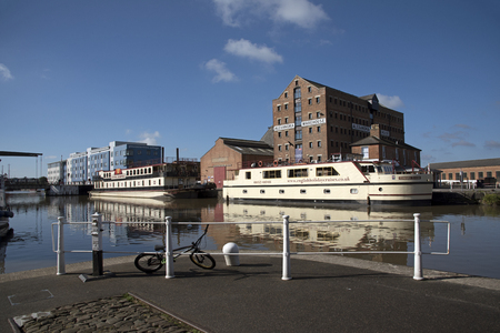 regenerated: Gloucester Docks Gloucestershire England UK - October 2016 - Commercial boats alongside in the main basin of these historic docks which date from 1827 with the blue building which is a part of the Gloucester College campus