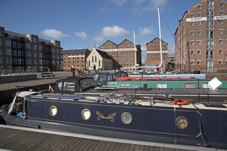 regenerated: Gloucester Docks Gloucestershire England UK - October 2016 - Narrowboats berthed with a backdrop of refurbish warehouse in the docks which date from 1827 Editorial
