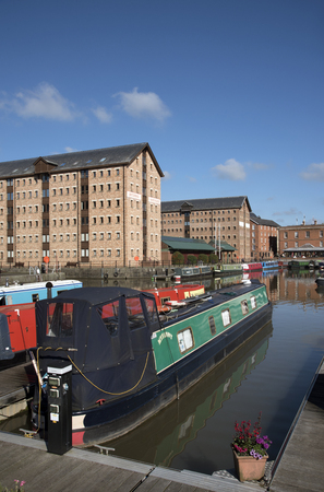 Gloucester Docks Gloucestershire England UK - October 2016 - Narrowboats berthed with a backdrop of refurbish warehouse in the docks which date from 1827 Editorial