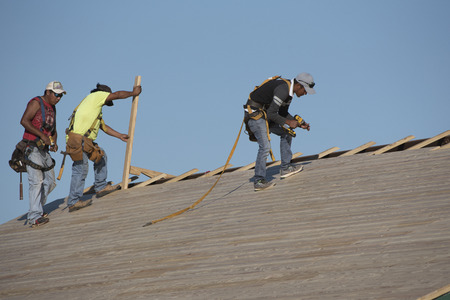 pitched: Florida USA - October 2016 - Team of roofers replacing a wooden roof