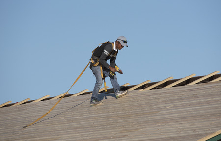 pitched roof: Florida USA - October 2016 - Roofer wearing a safety harnessand holding a drill to secure wooden slats on a pitched roof