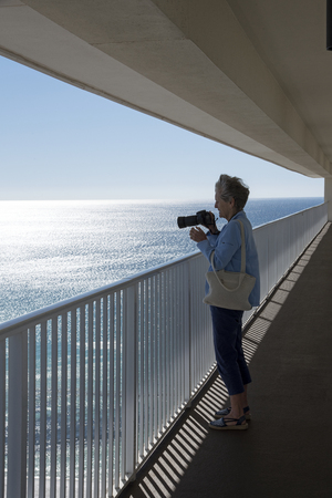 outside shooting: Gulf Coast Florida USA - October 2010 - Woman taking a photo of the Gulf coastlinefrom a highrise balcony