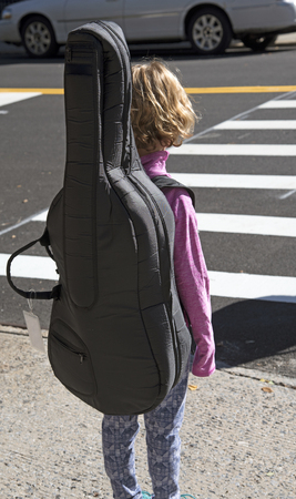 Bambina portando un violoncello in un caso in attesa sul marciapiede per attraversare una strada