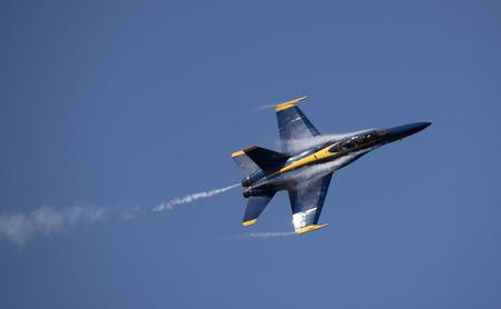 condensacion: avión militar que muestra el humo y la condensación contra un cielo azul