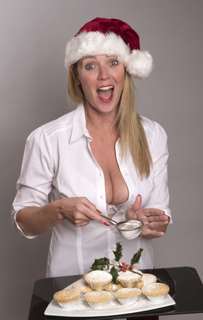 Woman in a Santa hat decorating the traditional Mince Pies with icing sugar