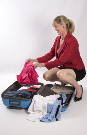 open suitcase: Woman packing an open suitcase