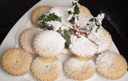 Traditional mince pies with a covering of icing sugar and a sprig of holly Stock Photo