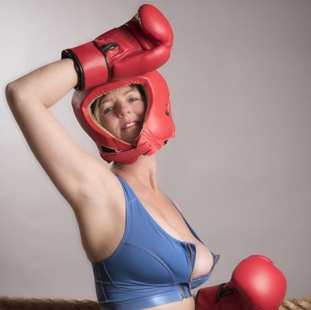 cabeza de mujer: Retrato de un boxeador femenino que lleva protector de cabeza roja y guantes