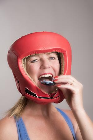 busty: boxeador de sexo femenino que lleva un guardia de seguridad de la cabeza y la inserción de un protector bucal en su boca