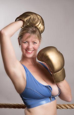 female boxer: Female boxer wearing gold coloured boxing gloves Stock Photo