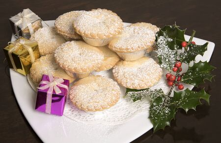 Traditional Mince pies with a dusting of icing sugar on a white plate Stock Photo