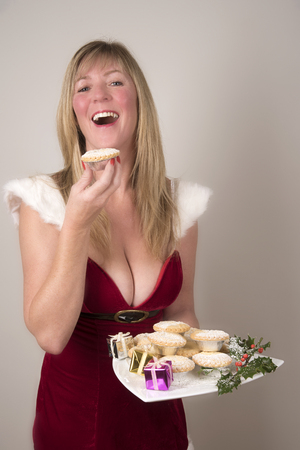 Party hostess eating a Mince pie at Christmastime