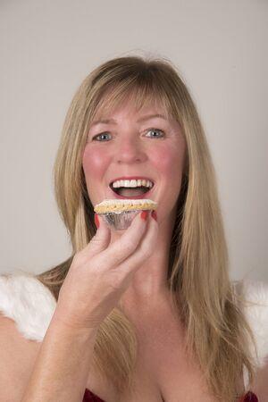 carne picada: presentadora de fiesta comiendo un pastel de carne en Navidad Foto de archivo