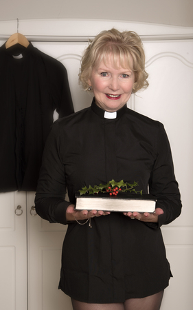 clerical: Woman vicar holding a sprig of Holly on a book