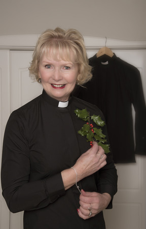 vicar: Woman vicar holding a sprig of Holly