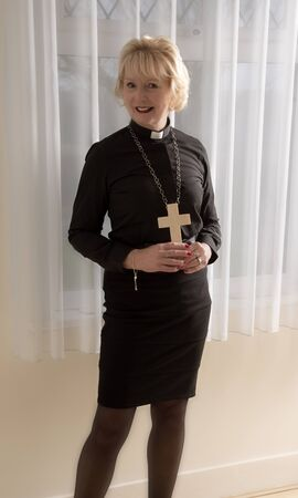 vicar: Woman vicar holding a wooden cross