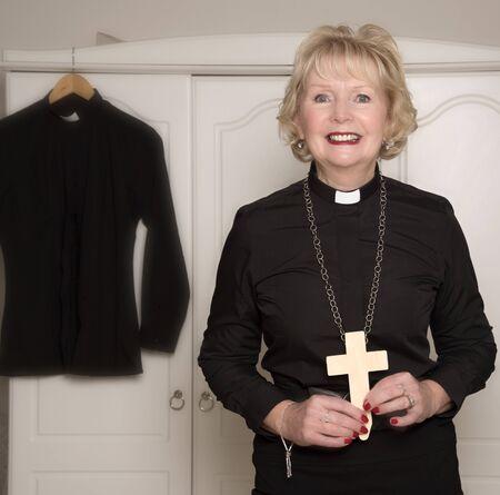 Portrait of woman vicar holding a wooden cross