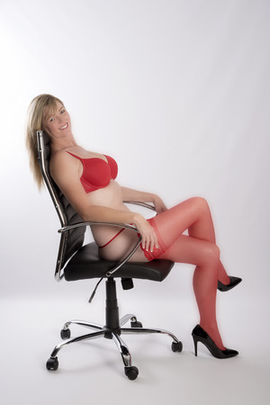 Blond secretary wearing red underwear with an executive office chair Stock Photo