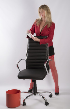 Sexy secretary wearing a short skirt and taking notes standing with an office chair Stock Photo